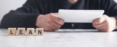 Man using tablet. LEAN word on the cubes
