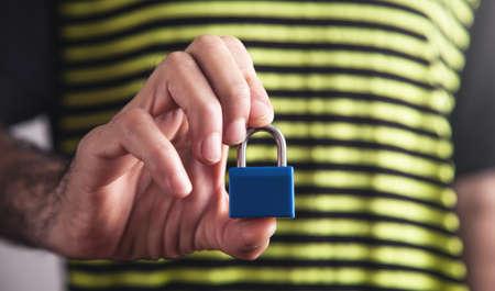 Man showing metal padlock. Security concept 스톡 콘텐츠