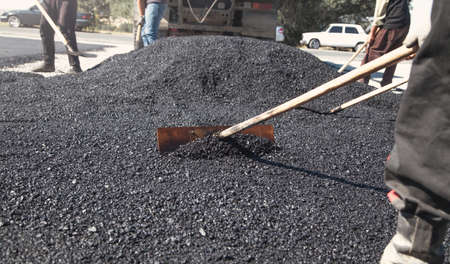 Workers arranging asphalt. Road construction. Industry