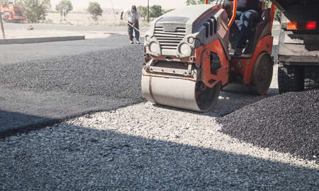 Asphalt roller stacking and pressing hot asphalt.