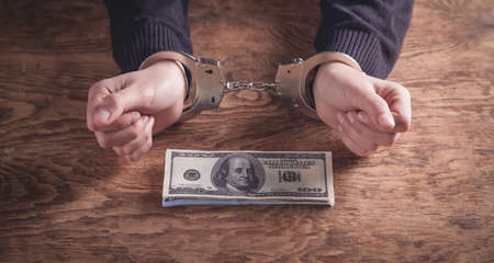 Hands in handcuffs holding dollar banknotes. Corruption