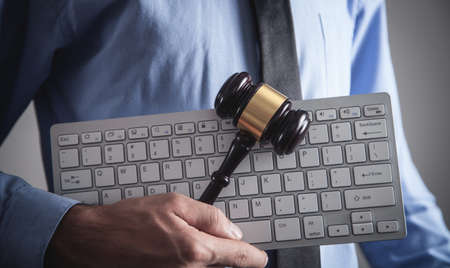 Man holding Judge gavel with computer keyboard. Concept of internet crime