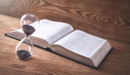 Hourglass with book on wooden table.