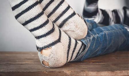 Male feet with ripped woolen socks.