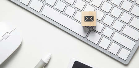 Email symbol on the wooden cube. Business desk
