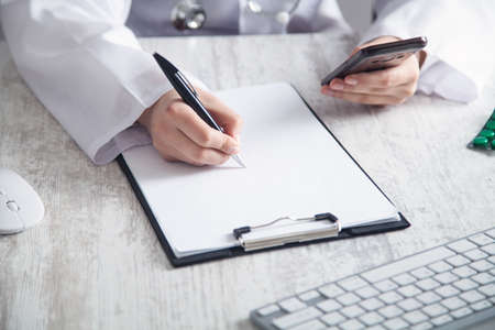 Doctor using smartphone and writing in a clipboard at clinic.