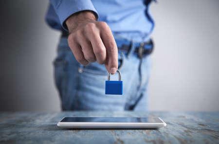 Man holding padlock.Tablet on the desk. Internet security