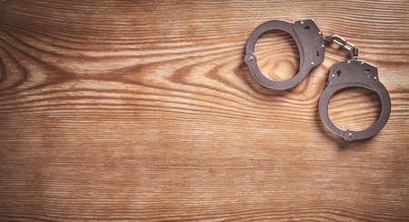 Metal handcuffs on wooden background.