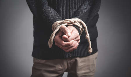 Man hands tied by a rope. Imprisonment