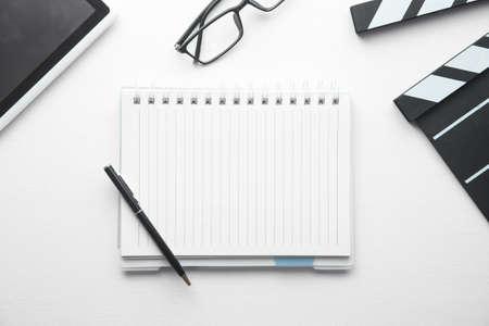 Movie clapper, notepad and other objects on white desk. Zdjęcie Seryjne