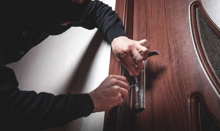 Robber with black mask trying to open door.