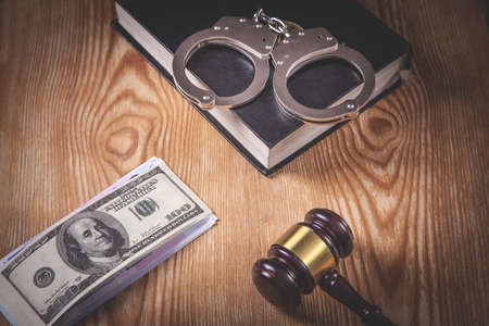 Metal handcuffs, book, money, gavel on the wooden background.