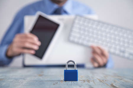 Padlock on the desk. Man holding tablet and computer keyboard. Internet and computer security