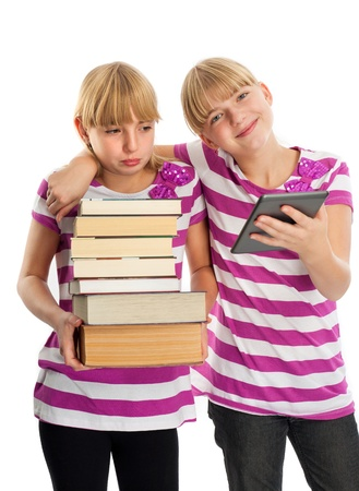 e book reader: Books vs ebook reader - Two girls demonstrating the difference  One of them holding lots of books while another reading an ebook reader and smiling