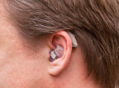 personas escuchando: Primer plano de un hombre con una oreja de alta tecnolog�a digital detr�s de la oreja para o�r dispositivo