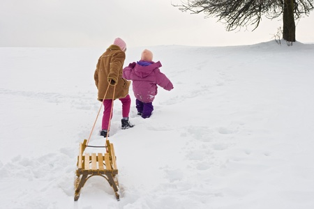 Two children climb up on a hill with a yellow sledge  photo