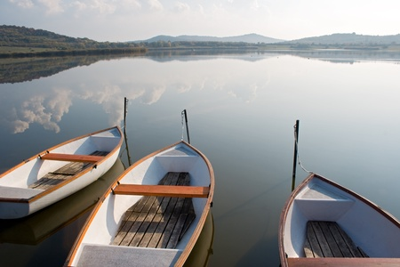 Three boats on a calm lake water surface mirroring the cloudy sky  Stock Photo