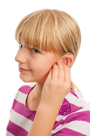 listening to people: Teen girl wearing a hearing aid. Studio shot-isolated on white background. Stock Photo
