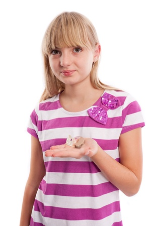impaired: Nice teen girl holding a hearing aid in front of a white background. Stock Photo