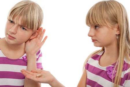 Girl offering a hearing aid to another girl who cant hear well. Isolated on white. photo