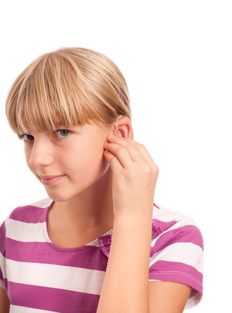 Hearing aid setting - Young Girl putting on her hearing aid. Isolatoed on white. photo