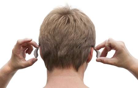 Back view of a deaf mans head and hands putting on his behind-the-ear hearing aid.