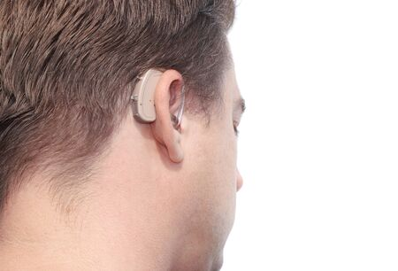 hearing aid: close-up of a man head with a behind-the-ear-hearing device.