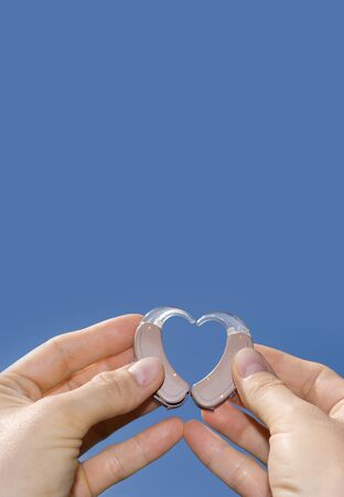 Hands showing a heart shape from digital hearing aids in fron of a blue sky background useful for text Stock Photo