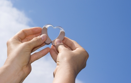 listening device: Hands showing a heart shape from digital hearing aids in fron of a blue sky background