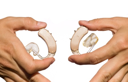 Hands show pair of hearing aids with earmoulds and tubing  Isolated on white  Stock Photo