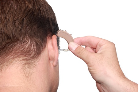 A deaf man putting on his behind-the-ear hearing aid