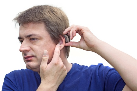 Middle-aged man putting on his hearing aid  Isolated on white