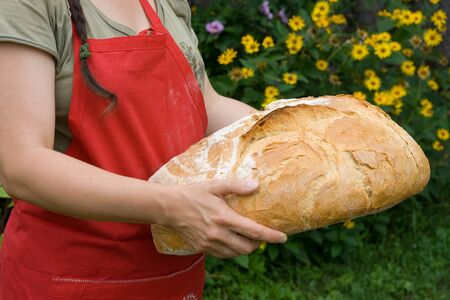 Girl wearing a red pinafore dress holds a hand made freshly baked bread. Stock Photo
