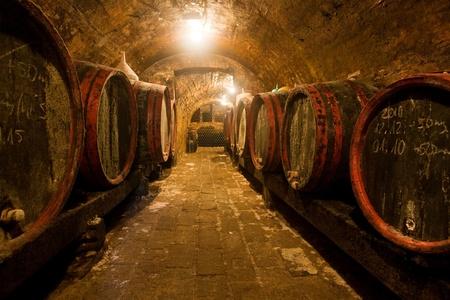 Weinfässer und Flaschen in einem traditionellen Weinkeller. Warme Farben, Weitwinkel. Standard-Bild
