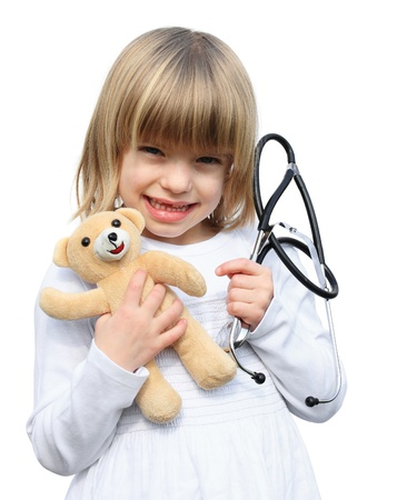 Little blonde girl doctor examines her teddy bear with a stetoscope. Isolated on white
