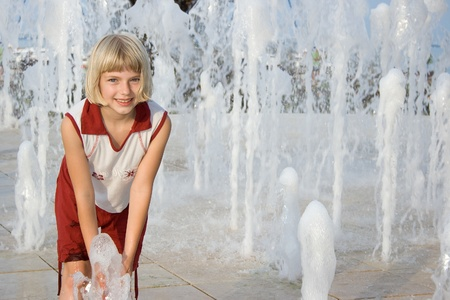 Smiling girl playing in a fountain on a hot summer day.  photo