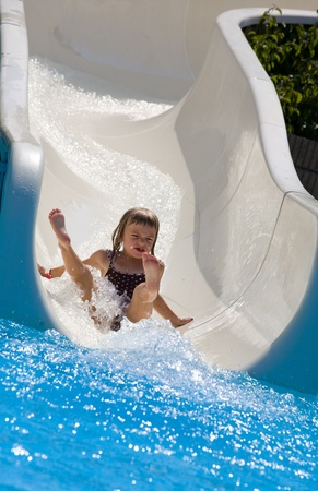 Small girl sliding down a water slide. Stock Photo