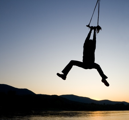 A young girl hanging on a rope wing above a river at sunset.  photo