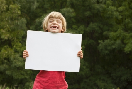 Cute girl holding a white board suitable for text.