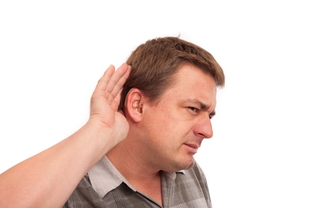 I cant hear you - Middle aged deaf man wearing hearing aids cupping hand behind ear on white background
