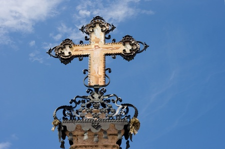 Ornate orthodox cross made from wrought iron and decorated with icon painting in front of a blue sky background. (Place: Szentendre, Hungary) Stock Photo - 17617658
