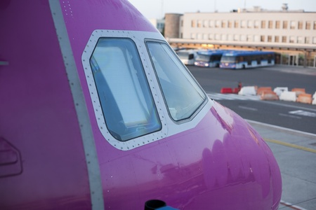 Detail of airplane nose with pilot cabin with an airport in the background. photo