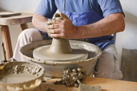 Clay in the potters wheel and hand