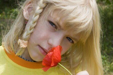 A nice small blonde girl smells a red poppy. Stock Photo