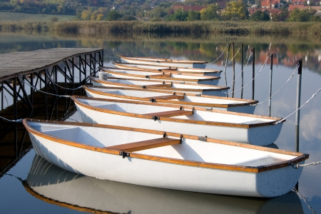 Seven white angler boats on a calm lake water surface at a boat harbor. Stock Photo - 17618146