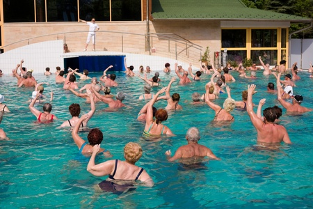 special education: Special education teacher leading a Group of gym people in a thermal swimming pool