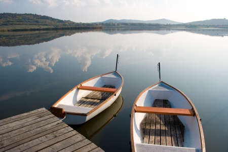 Two boats on a calm lake water surface mirroring the cloudy sky.