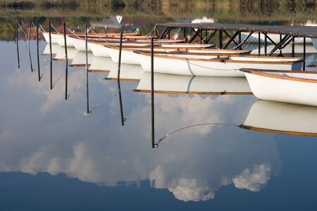 mirroring: Water mirroring white boats and the cloudy sky. Stock Photo