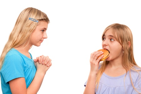 Girl begging for a piece of hamburger with folded hands to another girl. Isolated on white. Stock Photo - 18184256