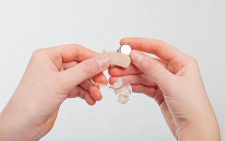 Hearing aid battery - Female hands changing a hearing aid battery.